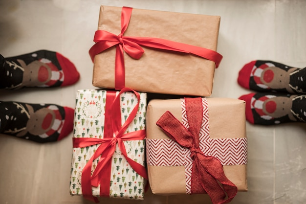 Person's legs in christmas socks near present boxes