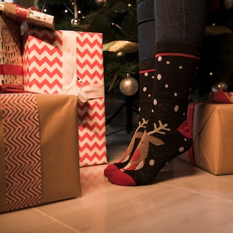 Person's legs in Christmas socks between present boxes and decorated fir tree