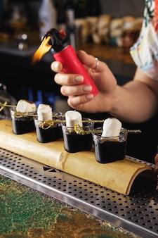 Человек, опаляющий зефир за ромом и кофейным коктейлем