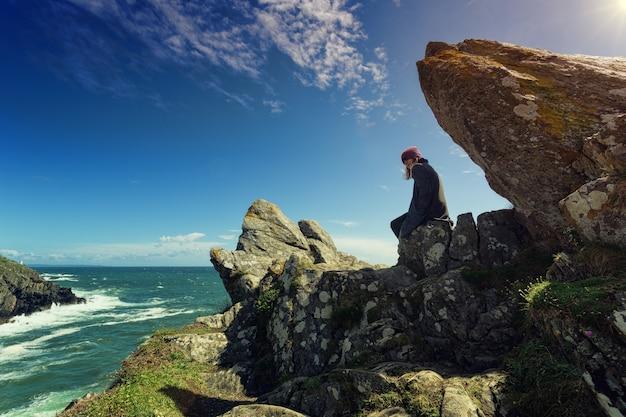 암석에 앉아있는 사람