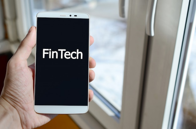 A person sees a white inscription on a black smartphone display that holds in his hand. fintech