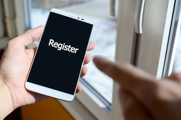 A person sees a white inscription on a black smartphone display that holds in his hand. register