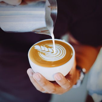 Person serving a cup of coffee with a metal jug