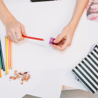 Person sharpening red pencil at table