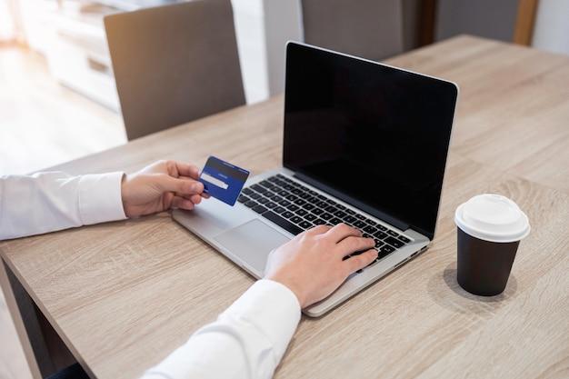 컴퓨터와 신용 카드로 온라인 쇼핑하는 사람