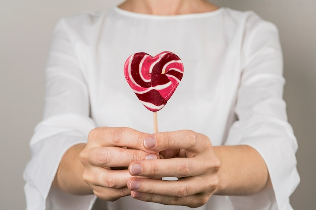 Person showing lollipop in form of heart