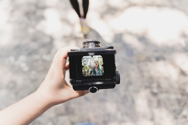A person showing photo of a woman on vintage camera