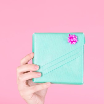 A person showing wrapped turquoise gift box on pink background