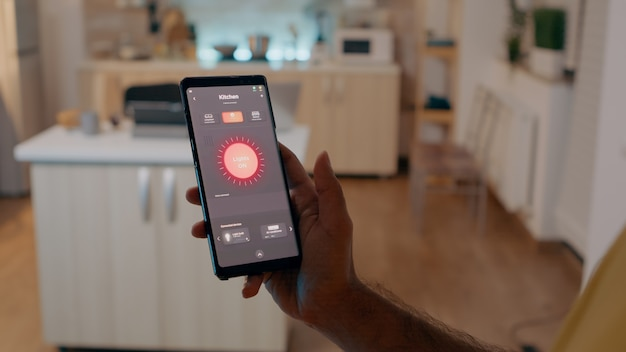 スマートフォンを持って電球をオンにし、スマートホームアプリケーションでワイヤレスルームの雰囲気を制御する自動照明システムを持って家に座っている人。最新のソフトウェアアプリを搭載したモバイル