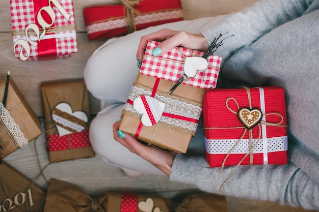 Persona seduta sulle ginocchia con diversi regali di san valentino