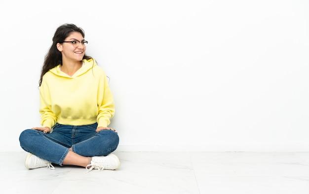 孤立した背景の上に床に座っている人
