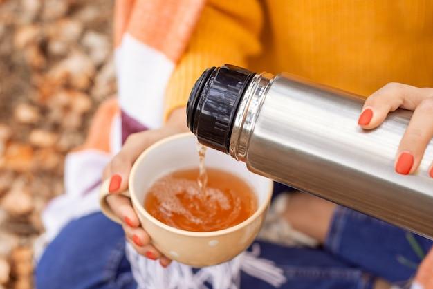 야외에 앉아 보온병의 차를 흰색 컵에 붓는 사람. 쌀쌀한 가을 날씨, 자연을 산책하며 따뜻한 음료.