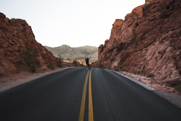 Person skating on a highway road surrounded by red rocks