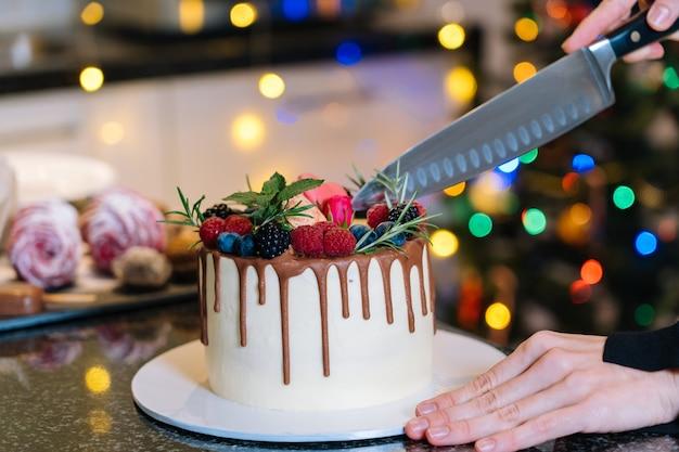 自家製のクリスマスフルーツケーキをスライスする人。明けましておめでとうとメリークリスマスの背景。デフォーカスクリスマスツリーライトと暗い背景の上の冬の装飾。セレクティブフォーカス。