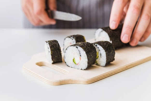 Person slicing sushi wrap on cutboard