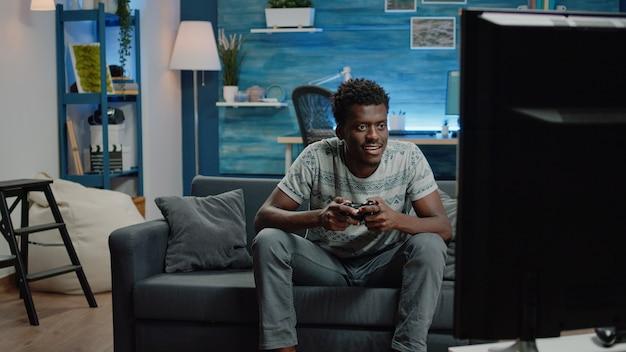 Человек улыбается после победы в видеоиграх по телевидению