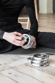 Person in sportswear sitting and assembling dumbbell