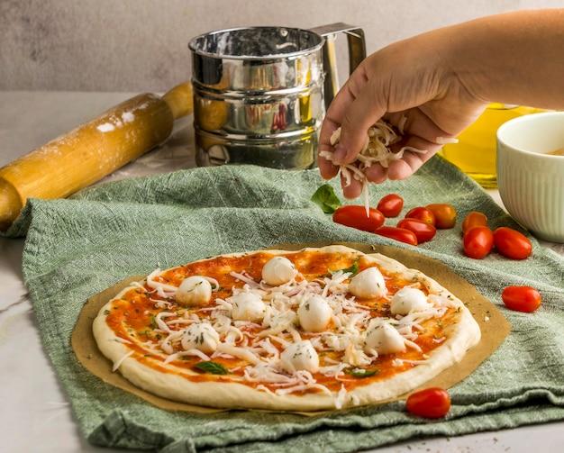 Человек посыпает пиццу сыром моцарелла