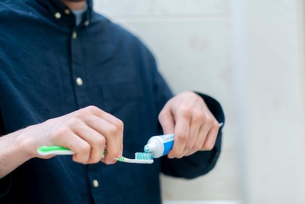 Человек выжимает зубную пасту на зубной щетке в ванной комнате