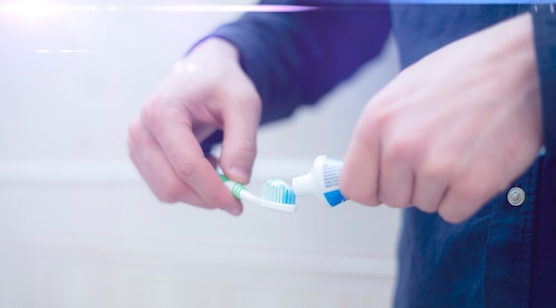 A person squeeze toothpaste on a toothbrush in bathroom