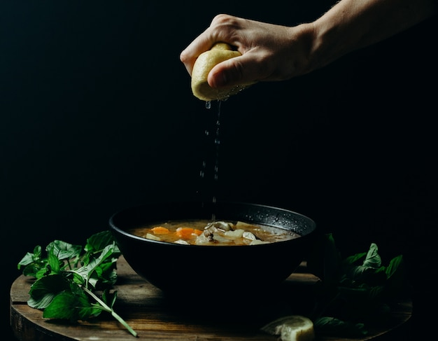 Person squeezing lemon on soup in a black bowl with a dark wall