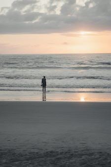 Person standing alone on a beach shore with the reflection of a setting sun