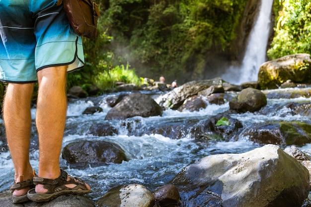Человек, стоящий у реки перед водопадом. турриальба, коста-рика