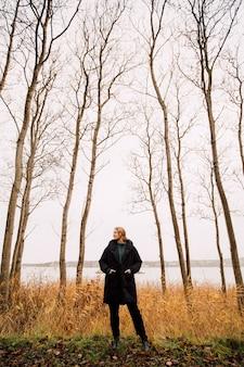 Persona in piedi in una foresta con un cappotto con le tasche nelle tasche