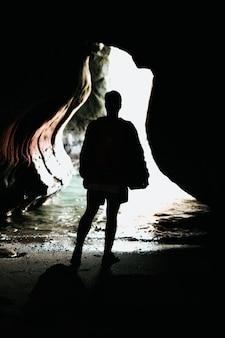 낮에 동굴 내부의 푸른 물 앞에 서 있는 사람