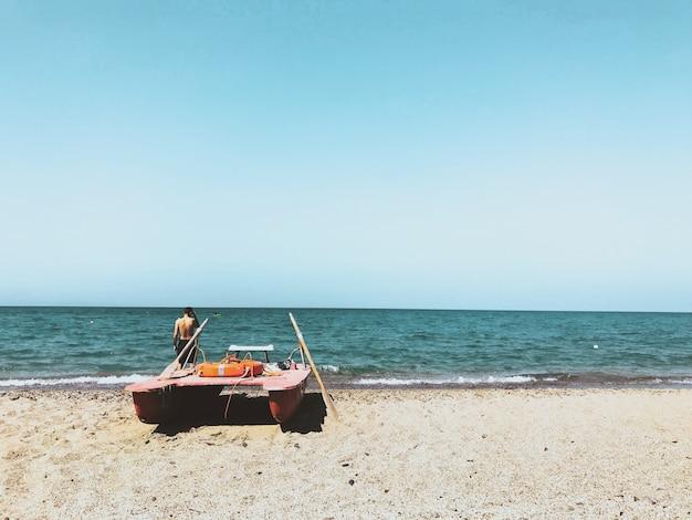 Человек, стоящий возле лодки на берегу пляжа с голубым небом