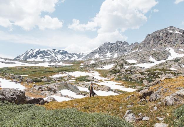 Человек, стоящий возле горы под облачным небом в дневное время
