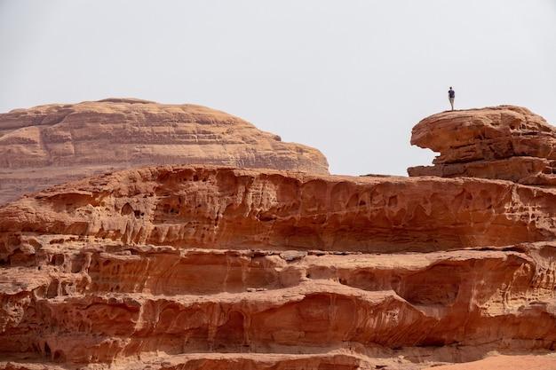 曇り空の下の砂漠の大きな崖の上に立っている人