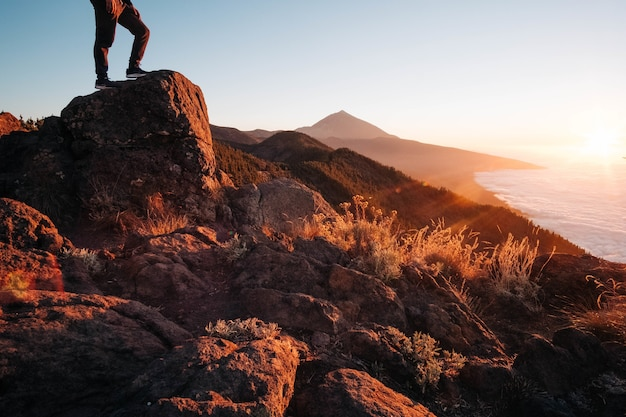 밝은 일몰 동안 바다로 둘러싸인 바위 위에 서 있는 사람 - 성공의 개념