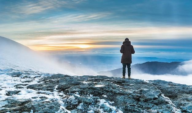 석양 아래 산의 숨막히는 전망을 통해 눈이 덮여 절벽에 서있는 사람