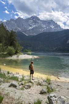 산으로 둘러싸인 독일의 eibsee 호수 해변에 서있는 사람