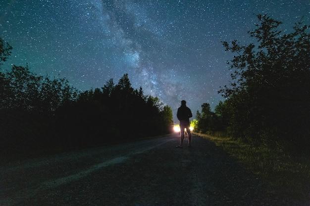 Человек, стоящий на дороге в ночное время