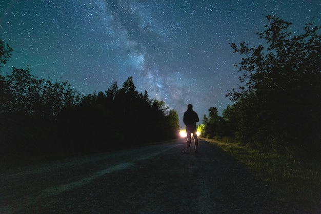 Person standing on road at night-time