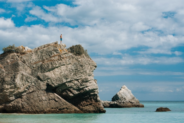 Person standing on top of a rock formation surrounded by a body of water during daytime