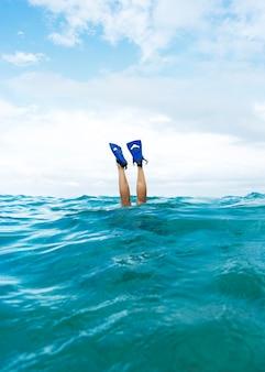 바다에서 수영하고 오리발을 착용하는 동안 다리를 펴는 사람