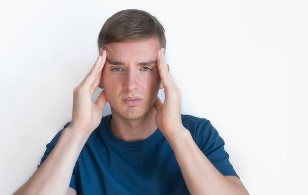 Человек страдает от боли, потому что сильная головная боль, мигрень. красивый красивый парень, молодой раздраженный расстроенный человек, держащий голову руками, виски с пальцами. выражение лица