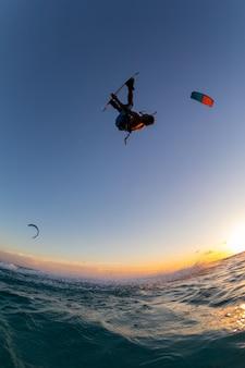 Человек занимается серфингом и полетом на парашюте одновременно в кайтсерфинге