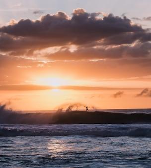 ビーチで日没時にサーフィンをする人