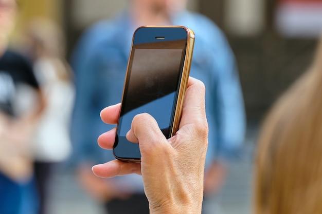 人は路上でスマートフォンで写真を撮ります。