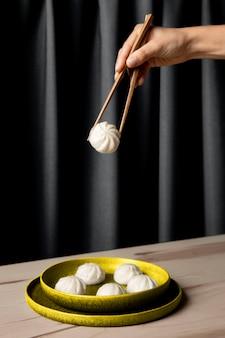 조명 접시에서 만두를 복용하는 사람