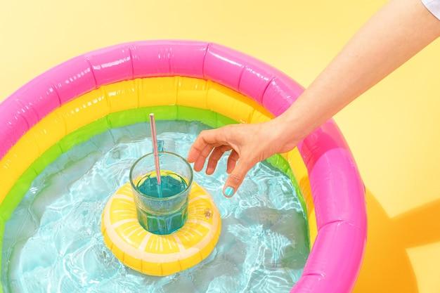 Человек берет надувной коктейль в форме лимона в детский бассейн Premium Фотографии
