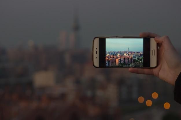 Человек фотографирует на свой мобильный