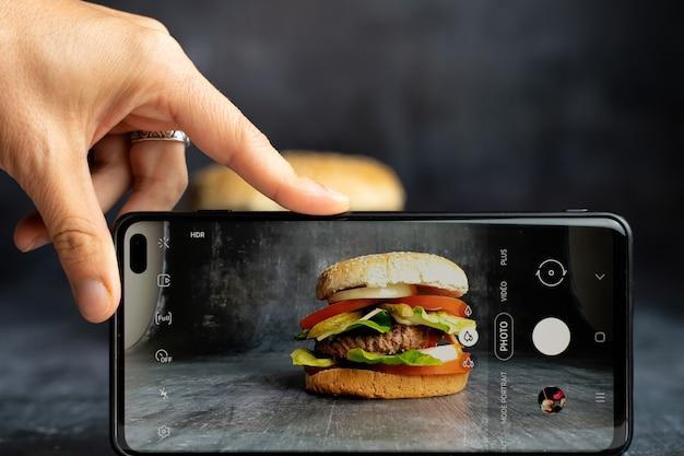 Человек, фотографирующий бургер ручной работы со смартфоном