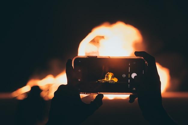 夜にスマートフォンで焚き火の写真を撮る人