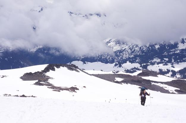 Человек, прогуливающийся в национальном парке маунт-рейнир зимой