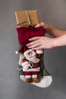 Человек, принимающий подарочную коробку из рождественского носка Бесплатные Фотографии